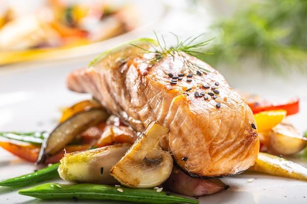 Saumon norvégien cuit sain servi avec légumes et champignons grillés.