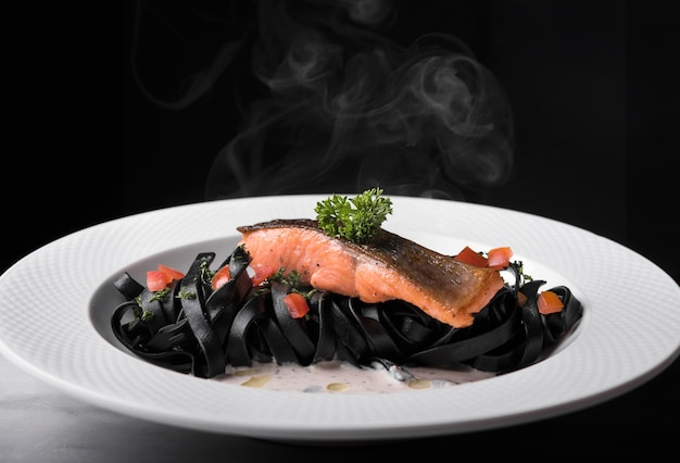 Saumon et pâtes noires avec tomates et persil sur plaque sur fond noir.