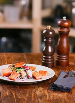 Saumon de poisson rouge aux radis et aux épinards, servi sur une assiette blanche sur une table en bois. style rustique. vue d'en haut, top studio shot