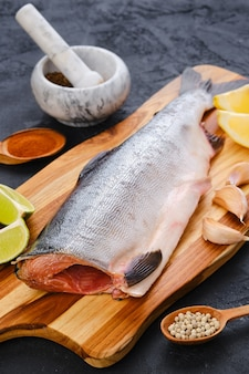 Saumon rose frais cru sans tête sur une planche à découper en bois