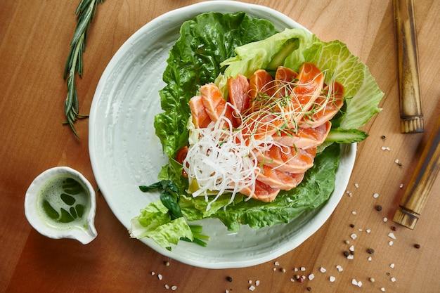 Saumon sashimi frais et délicieux et avec des verts dans un bol blanc sur une surface en bois