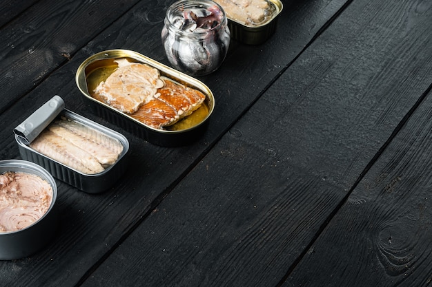 Saumon, thon, maquereau truite et anchois - poisson en conserve dans des boîtes de conserve, sur table en bois noir