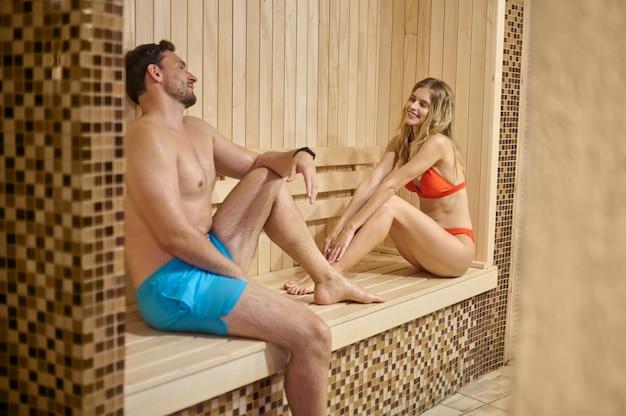 Sauna. un couple looing détendu tout en passant du temps dans un sauna ensemble
