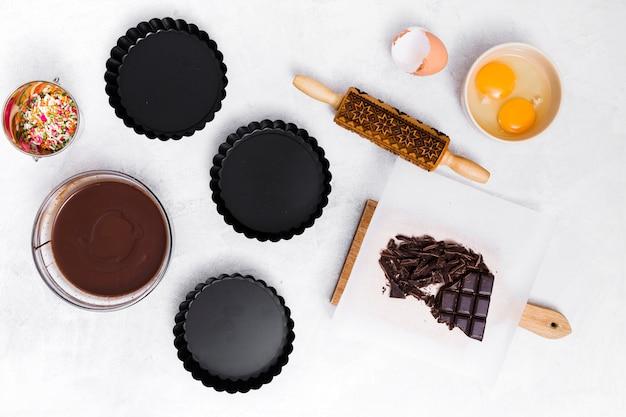 Saupoudrer; jaune d'œuf; rouleau à pâtisserie; barre de chocolat; sirop et trois porte-gâteaux vides sur fond blanc