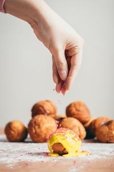 Saupoudrer le sucre sur un beignet.