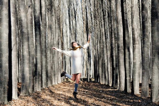 Saut femme enthousiaste et rire dans la forêt