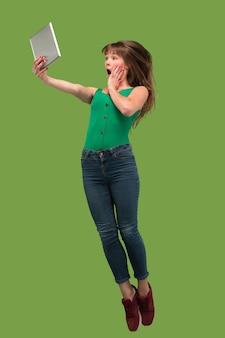 Saut de jeune femme sur fond de studio vert à l'aide de gadget ordinateur portable ou tablette en sautant.