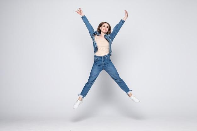 Saut de jeune femme en jeans sur mur blanc