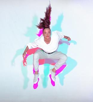 Saut d'une jeune fille élégante de race mixte sur fond blanc arc-en-ciel studio coloré lumière ardente hanche