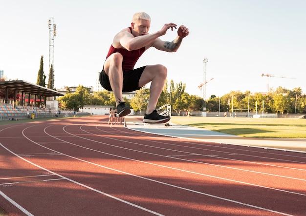 Saut en longueur d'athlète homme de race blanche