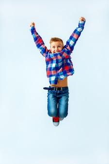 Saut petit garçon dans la chemise à carreaux colorée, blue jeans, gumshoes. isolé.