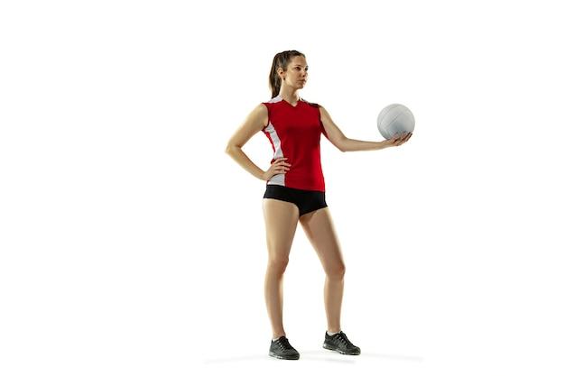 En saut et en vol. jeune joueuse de volley-ball isolée sur fond de studio blanc. femme en vêtements de sport et baskets s'entraînant, jouant. concept de sport, mode de vie sain, mouvement et mouvement.