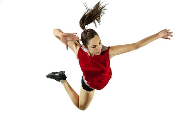 En saut et en vol. jeune joueuse de volley-ball isolée sur fond de studio blanc. femme en vêtements de sport et chaussures de sport, jouant. concept de sport, mode de vie sain, mouvement et mouvement.