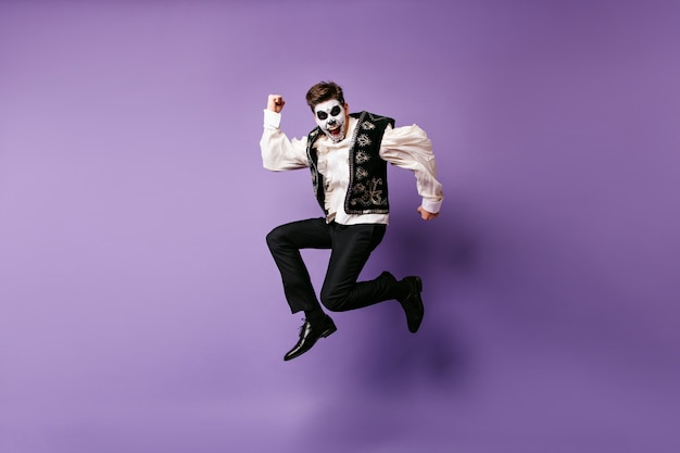 Sautant homme riant en costume d'halloween. photo intérieure d'un mec excité avec du maquillage mexicain dansant sur un mur violet.
