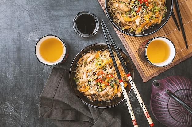 Sauté au wok nouilles avec du poulet et des légumes dans une assiette sur une surface sombre, vue du dessus