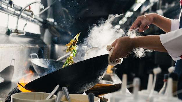 Sauté de chef cuisinier occupé dans la cuisine. le chef fait sauter les aliments dans une poêle, fumer et éclabousser la sauce dans la cuisine.