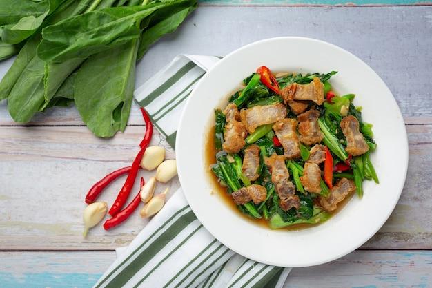 Sauté de chou frisé, porc croustillant épicé sur table en bois concept de cuisine thaïlandaise.