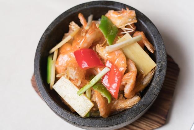 Sauté de crevettes dans un wok avec des assiettes de service dans le