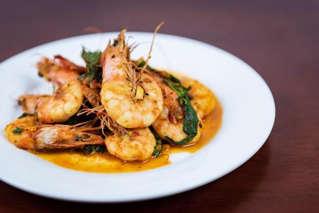 Sauté de curry rouge aux crevettes, cuisine thaïlandaise sur fond en bois