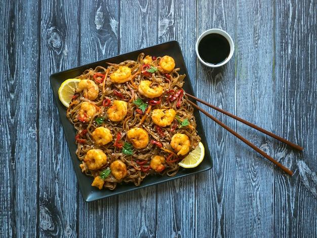 Sauté de nouilles aux crevettes frites, légumes et sauce soja. table de cuisine asiatique.