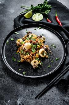 Sauté de nouilles faites maison avec des fruits de mer et des légumes dans une assiette.