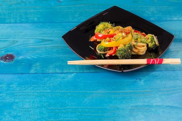Sauté de nouilles japonaises avec légumes sur une plaque noire