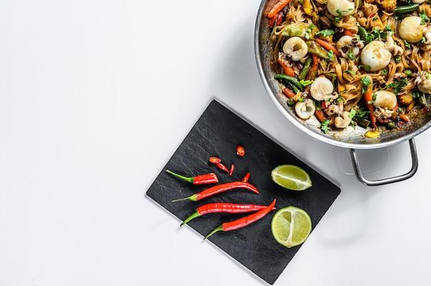 Sauté de nouilles udon aux fruits de mer et légumes. fond blanc. vue de dessus. espace copie