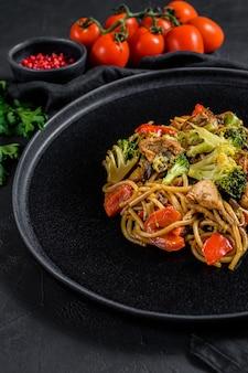 Sauté de nouilles, wok chinois traditionnel. baguettes, ingrédients.