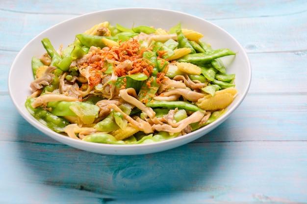 Sauté de pois mange-tout au maïs et aux champignons en plaqué blanc.