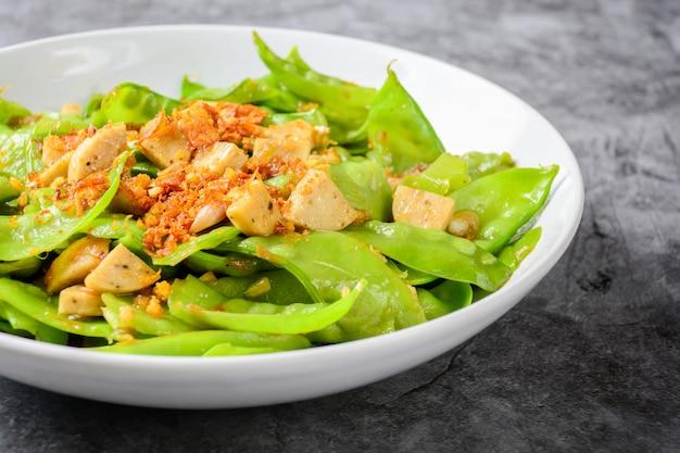 Sauté de pois mange-tout avec des saucisses de porc grillées vietnamiennes, garnies d'échalotes frites croustillantes et d'ailes