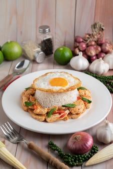 Sauté de poulet à la pâte de chili avec du riz œufs frits dans une assiette blanche sur une table en bois.