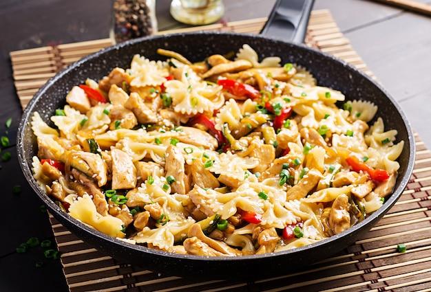 Sauté de poulet, pâtes farfalle, courgettes, poivrons et oignons verts