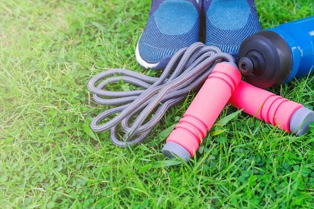 Sauter à la corde, chaussures de course et boire une bouteille sur fond d'herbe