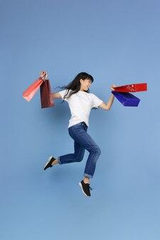 Sauter haut avec des sacs à provisions