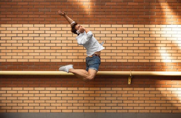 Sauter jeune homme d'affaires devant les bâtiments, sur la course en saut en hauteur