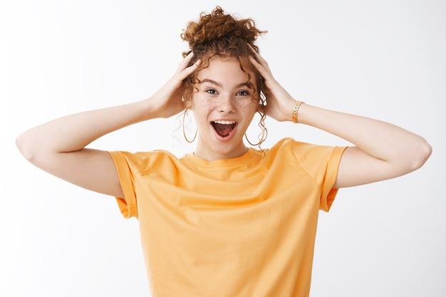 Sauvage émotif énergisé belle jeune fille rousse des années 20 chignon bouclé désordonné portant un t-shrit orange criant amusé s'amusant debout humeur joyeuse touchant la tête ravie, fond blanc