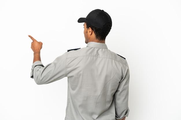 Sauvegarde afro-américaine sur fond blanc isolé pointant vers l'arrière avec l'index