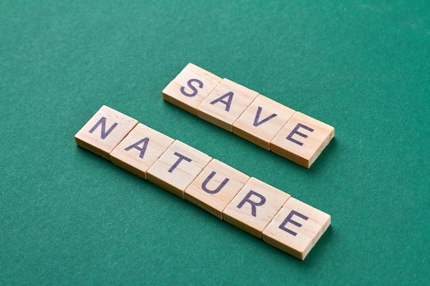 Sauver le concept de la nature. blocs de lettres en bois isolés sur fond vert.