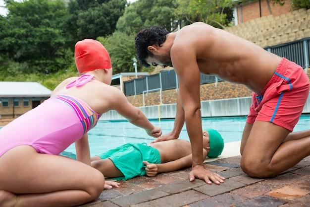 Sauveteur aidant un garçon inconscient tout en interagissant avec une fille près de la piscine