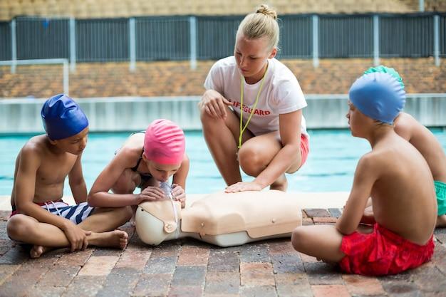 Sauveteur féminin aidant les enfants pendant la formation de sauvetage au bord de la piscine