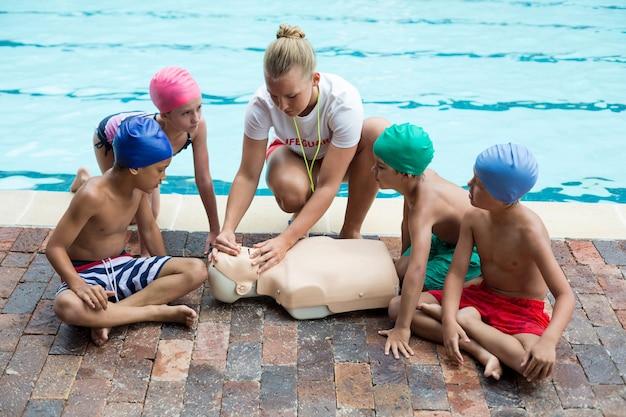 Sauveteur féminin donnant une formation de sauvetage aux enfants au bord de la piscine