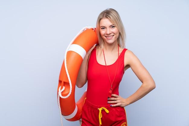 Sauveteur femme sur mur bleu isolé avec équipement de sauveteur et avec une expression heureuse