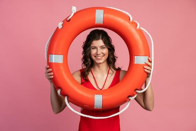 Un sauveteur gentil et souriant regarde à travers la bouée de sauvetage. jolie fille en maillot de bain rouge sur fond rose