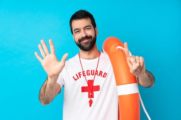 Sauveteur homme sur mur bleu isolé comptant six avec les doigts