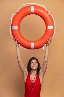 Un sauveteur mignon tient une bouée de sauvetage au-dessus de sa tête, levant les yeux. belle fille en maillot de bain sur fond orange