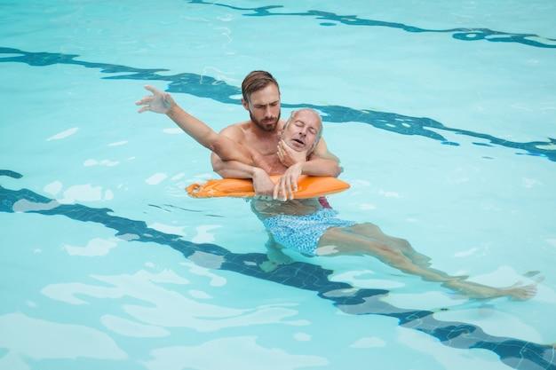 Sauveteur sauvant un homme âgé inconscient de la piscine