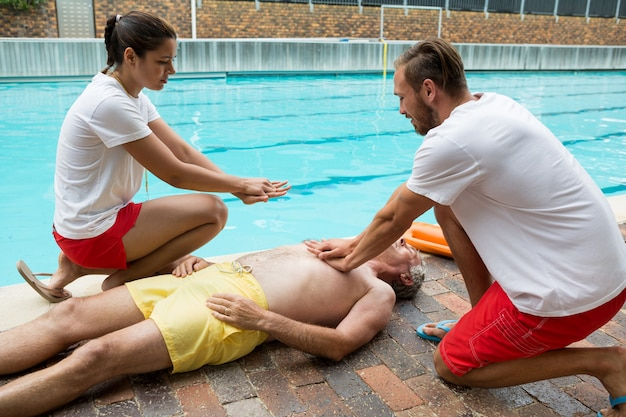 Les sauveteurs en appuyant sur la poitrine de l'homme senior inconscient au bord de la piscine