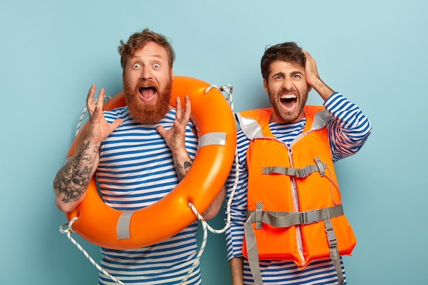 Des sauveteurs émotionnels horrifiés travaillent sur la plage en tant que sauveteurs, tiennent une bouée de sauvetage, portent un gilet de protection orange