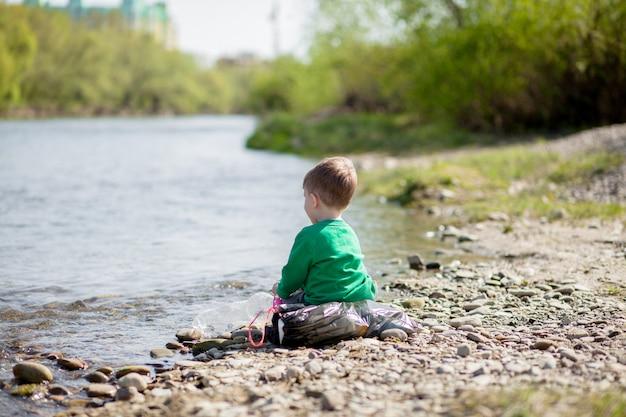 Sauvez le concept d'environnement, un petit garçon ramassant des ordures et des bouteilles en plastique sur la plage pour les jeter à la poubelle.