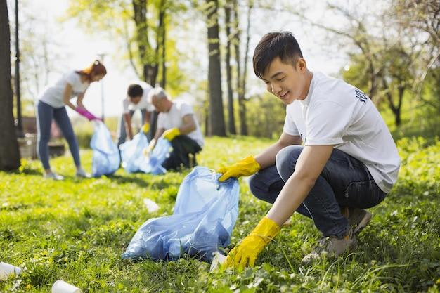 Sauvez la nature. heureux homme bénévole à l'aide d'un sac à ordures lors de la collecte des déchets